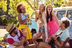 Groupe d'amis jouant la musique et ayant l'amusement ensemble Photos stock