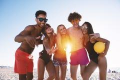 Groupe d'amis jouant ? la vol?e de plage ? la plage Matin, lumi?re du soleil photographie stock libre de droits