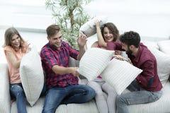 Groupe d'amis jouant le combat d'oreiller, s'asseyant sur le divan Photo stock