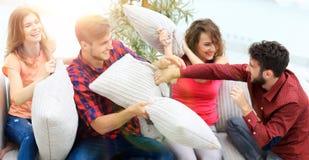 Groupe d'amis jouant le combat d'oreiller, s'asseyant sur le divan Photo libre de droits