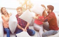 Groupe d'amis jouant le combat d'oreiller, s'asseyant sur le divan Images stock