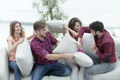 Groupe d'amis jouant le combat d'oreiller, s'asseyant sur le divan Image stock