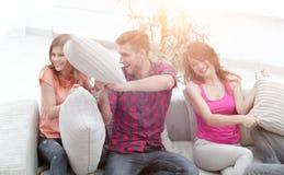 Groupe d'amis jouant le combat d'oreiller, s'asseyant sur le divan Photographie stock