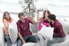 Groupe d'amis jouant le combat d'oreiller, s'asseyant sur le divan Images libres de droits