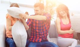 Groupe d'amis jouant le combat d'oreiller, s'asseyant sur le divan Photos stock