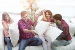 Groupe d'amis jouant le combat d'oreiller, s'asseyant sur le divan Image libre de droits
