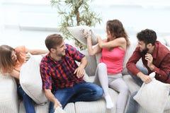 Groupe d'amis jouant le combat d'oreiller, s'asseyant sur le divan Photographie stock libre de droits