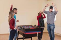 Groupe d'amis jouant le Tableau Foosball du football Photo libre de droits