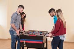 Groupe d'amis jouant le Tableau Foosball du football Image libre de droits