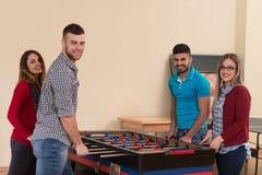 Groupe d'amis jouant le Tableau Foosball du football Photographie stock libre de droits