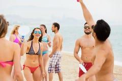 Groupe d'amis jouant le tennis à la plage Photos libres de droits