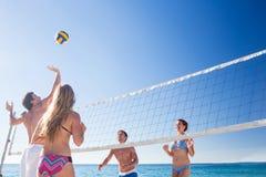Groupe d'amis jouant le volleyball Photographie stock libre de droits