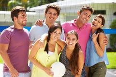 Groupe d'amis jouant le volleyball dans le jardin Photo stock