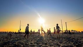 Groupe d'amis jouant le volleyball sur la plage Image stock