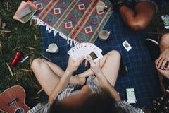 Groupe d'amis jouant un jeu de carte Images libres de droits