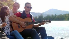 Groupe d'amis joyeux sur la plage jouant la guitare un jour d'été à côté de la rivière de montagne Photos libres de droits
