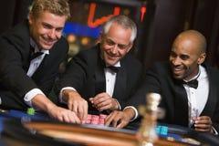 Groupe d'amis mâles à la table de roulette Photographie stock