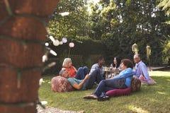 Groupe d'amis mûrs appréciant des boissons dans l'arrière-cour ensemble Photos libres de droits