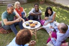 Groupe d'amis mûrs appréciant des boissons dans l'arrière-cour ensemble Photo libre de droits