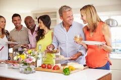 Groupe d'amis mûrs appréciant le buffet au dîner Photos libres de droits