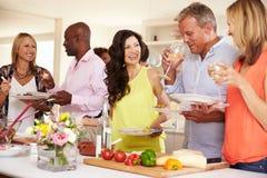 Groupe d'amis mûrs appréciant le buffet au dîner Photo stock