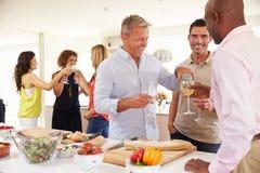 Groupe d'amis mûrs appréciant le dîner à la maison Photographie stock