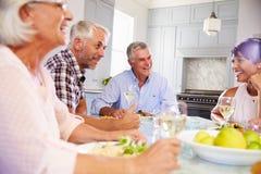 Groupe d'amis mûrs appréciant le repas à la maison ensemble Images stock