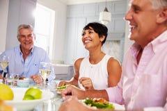 Groupe d'amis mûrs appréciant le repas à la maison ensemble Photographie stock