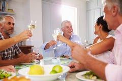 Groupe d'amis mûrs appréciant le repas à la maison ensemble Photos libres de droits