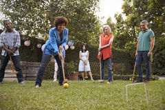 Groupe d'amis mûrs jouant le croquet dans l'arrière-cour ensemble photos stock