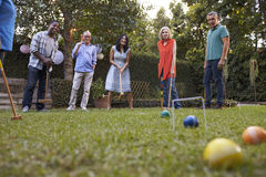 Groupe d'amis mûrs jouant le croquet dans l'arrière-cour ensemble images stock