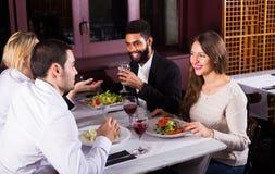 Groupe d'amis mangeant au restaurant Photos stock