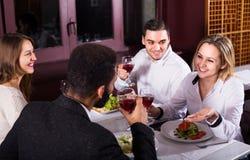 Groupe d'amis mangeant au restaurant Images stock