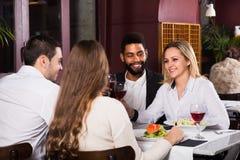 Groupe d'amis mangeant au restaurant Photographie stock libre de droits