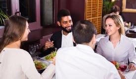 Groupe d'amis mangeant au restaurant Photographie stock