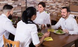 Groupe d'amis mangeant au restaurant et à la causerie Photographie stock libre de droits