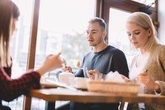 Groupe d'amis mangeant dans un restaurant Image libre de droits