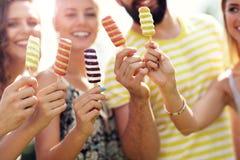 Groupe d'amis mangeant de la glace dehors Images libres de droits