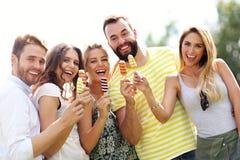 Groupe d'amis mangeant de la glace dehors Photo libre de droits
