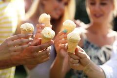 Groupe d'amis mangeant de la glace dehors Photos stock