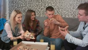 Groupe d'amis mangeant de la pizza à emporter et buvant du jus d'orange Image libre de droits