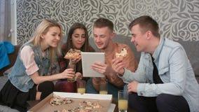 Groupe d'amis mangeant de la pizza à emporter et observant le programm sur le comprimé Image stock