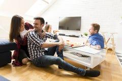 Groupe d'amis mangeant de la pizza ensemble à la maison Images libres de droits