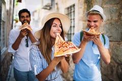 Groupe d'amis mangeant de la pizza tout en voyageant des vacances image libre de droits