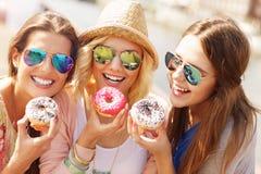 Groupe d'amis mangeant des butées toriques dans la ville Photographie stock