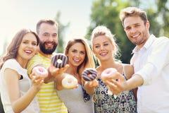 Groupe d'amis mangeant des butées toriques dehors Photographie stock libre de droits