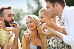 Groupe d'amis mangeant des butées toriques dehors Photos stock