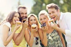 Groupe d'amis mangeant des butées toriques dehors Images stock