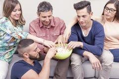 Groupe d'amis mangeant du maïs éclaté sur le sofa Photos libres de droits
