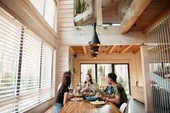 Groupe d'amis mangeant et parlant sur la cuisine Photo stock